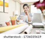Small photo of young asian business woman working at home using laptop computer and digital tablet (artwork in background digitally altered)