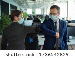 Small photo of Two colleagues avoid a handshake when meeting in the office and greet bumping elbows. Greetings in Wuhan. A man and a woman in medical masks maintain a social distance at work.