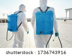 Small photo of Sanitization and disinfection of the city due to the emergence of the Covid19 virus. Specialized team in protective suits and masks with backpack of pressurized spray disinfectant water. Rear view