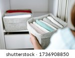 Small photo of Woman organizing clothes in wardrobe, putting shirts in boxes, baskets into shelves and drawer. Concept of minimalism lifestyle and japanese t-shirt folding system. Tidy up closet