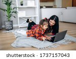 Small photo of Friendly relations of mom and her cute little daughter. They wallow at home on the floor in casual clothes and shopping online together using a laptop. They buy new toys for pretty little girl