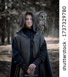Small photo of Art photo of a warlike youth in a woolen coat with a large owl on his shoulder