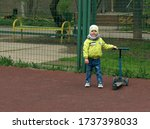 Small photo of The boy rides a blue scooter on a sports plod. Selective focus image.