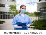 Female doctor holding blue clipboard standing outside hospital or clinic,frontline key medical worker portrait in modern care facility or nursing home complex yard,Coronavirus pandemic outbreak crisis