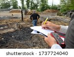 Small photo of Normandy, France, May 2015. Accidental fire in a farm. Farm building and farm equipment calcined. Rubble. Determination of the damages, farmer with the adjuster