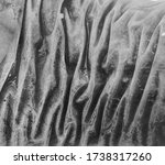 Macro shot of frozen wrinkled fish texture. Puckered, shrunken natural background. Frozen waves, surreal abstract pattern - stock photo