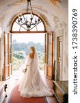 Small photo of Wedding at an old winery villa in Tuscany, Italy. The bride walks in the interior of the villa, overlooking the garden.