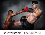 caucasian boxer making kick in defense to african american boxer who making yap punce in kick boxing or muay thai fight match, selective focused
