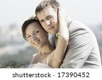 Portrait smiling groom and bride against sky - stock photo