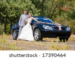 Groom and bride joy against backdrop wedding car decorated with flowers - stock photo