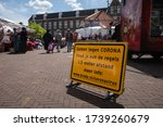 """Small photo of BREDA - MAY 23: warning sign against coronavirus at market on 23 May 2020, in Breda,The Netherlands. Translation:""""Together against CORONA. Abide the rules.1,5 meter distance. More info:www.breda.nl"""""""