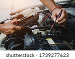 Auto mechanic using measuring equipment for checking car battery. Concepts of car Repair service and car insurance. - stock photo