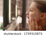 Small photo of A beautiful woman washes her skin on her face in the bathroom by the mirror. side view . Healthy facial skin. Skin care. Pore cleansing.