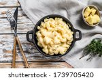 Small photo of American mac and cheese, macaroni pasta in cheesy sauce. White wooden background. Top view