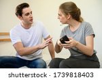 Small photo of Young Caucasian woman feeling angry and quarrel with boyfriend after found hidden love affair evidence in smartphone. Love affair couple relation problem concept.
