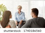 Small photo of Happy Family Psychologist Smiling Looking At Couple's Reconciliation During Therapy Session Sitting In Office. Selective Focus