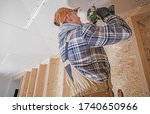 Caucasian Construction Contractor with Electric Drill Driver Attaching Drywall Elements to the House Ceiling. Finishing Home Interior.  - stock photo