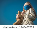 Covid 19 Pandemia Theme. Caucasian Girl in Blue Face Mask Holding Large Teddy Bear Showing Thumbs Up During Global Virus Outbreak. - stock photo