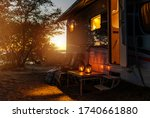 Road Trip Adventures. Calm Warm Night on a Camping. Camper Van, Outdoor Chairs and Romantic Light From Lanterns. Vacation in Recreational Vehicle. - stock photo
