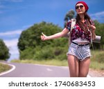 Small photo of Travel woman hitchhiking with backpack and red hat. A female hitchhiker by the road during vacation trip.The concept of traveling and hitchhiking.