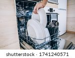 Woman loading the dishwasher. Open dishwasher with clean glasses and dishes close-up after washing. Clean  in open dishwashing machine. - stock photo