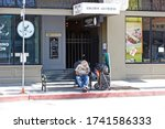 PASADENA/CALIFORNIA - MAY 24, 2020: Image of a homeless man sitting on a bus bench, depicting the growing epidemic of homelessness in southern California. Pasadena, California USA - stock photo