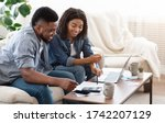 Small photo of Household Budget. Smiling Black Couple Discussing Total Amount Of Their Spends At Home, Happy About Wise Planning