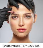Small photo of Young caucasian woman getting botox cosmetic injection in a forehead. Beautiful woman gets botox injection in her face. Adult girl gets cosmetic injection of botox in a clinic. Beauty treatments