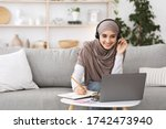 Online Education For Muslim Women. Happy Arabic Girl In Headscarf And Headset Studying With Laptop At Home, Taking Notes While Watching Webinar