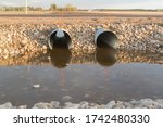 Steel culverts reflecting in water