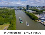 aerial drone footage of canal in the province of Utrecht with inland freight ships passing by. The Netherlands. inland vessel. in the back is the A12 highway with the prins clausbrug / galecopperbrug