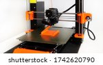 Small photo of 3D Printer in operation with orange filament on a white background - FFF (Fused Filament Fabrication) or FDM (Fused Deposition Modelling). Home 3D open-source DIY printer