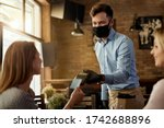 Small photo of Female customer making contactless payment to a waiter who is wearing protective face mask in a cafe.