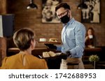 Happy waiter wearing protective ...