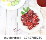 Small photo of Delicious Chinese Cuisine Ayam Char Siu or Grilled Char Siu Chicken or Char Siew, vibrant red chicken made from angkak or red yeast rice. Served in white plate on wooden table. Selective focus.
