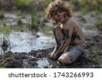 A Young Boy Is Covered In Mud...