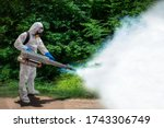 Small photo of Health center staff spraying the smoke to get rid of mosquitoes at forest for stop spreading infections dengue fever and malaria