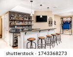 Small photo of CHICAGO, IL, USA - FEBRUARY 24, 2020: A small basement bar /man cave with liquor on shelves and the bar is surrounded by wood bar stools. A basketball game is setup in the background.