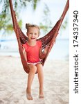 Adorable little girl swinging in hammock at beach - stock photo