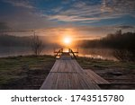 Dawn Over A Misty Lake With A...