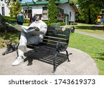 Small photo of Katikati New Zealand - January 6 2014 - Bronze statue of man sitting on park bench reading newspaper in centre of township, named Barry - a kiwi bloke.