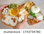 Chef's hand holds the cheese plate. Cheese mix on a wooden plate decorated with grapes, nuts, salad and olives with cheese knifes - stock photo