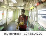 Small photo of MUMBAI/INDIA - MAY 28, 2020: A worker sprays disinfectant to sanities a monorail as a preventive measure against the COVID-19 corona virus. MMRDA is preparing to resume its services.