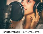 Female Voiceover Speaker in Her 20s Inside Recording Studio in Front of Professional Microphone. - stock photo