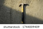 Flat lay of dirty metal hammer on grunge cement background with natural light and shadow. Consist of a weighted head fixed to a long handle that is swung to give an impact to small area of an object. - stock photo