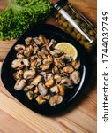 Small photo of Mussel meat on a wooden Board on a wooden table. Mussel meat with lemon. Mussel meat with lemonFresh raw mussel meat and lemon.
