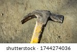 Close up view of dirty head metal hammer on grunge background with natural light and shadow. Consist of weighted head fixed to a long handle that is swung to give an impact to small area of an object. - stock photo
