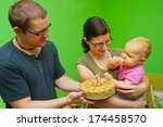 fist birthday with her parents - stock photo
