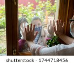 An elderly woman runs her hand through the window from the inside of her house, touching the arms of her granddaughters visiting her outside during the coronavirus pandemic - stock photo
