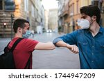 Two young friends meet in the city wearing protective masks from the Corona virus, Covid-19, Millennials greet each other with their arms and elbows protecting themselves from the Coronavirus